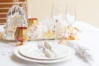Tableware for christmas - set of plates, cups and utencils with white table cloth and christmas golden decorations