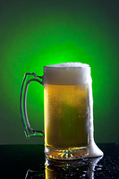 Foam runs down the side of a large mug of beer.