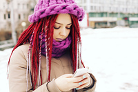 Girl wearing winter clothing, uses mobile phone