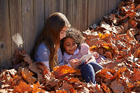 Kid girls friends playing tablet pc in autumn leaves park mixed ethnicity