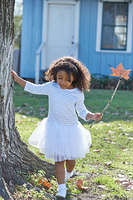 Kid toddler girl with autumn leaf magic wand playing outdoor park latin ethnicity