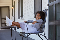 Kid toddler girl sitting in the park house porch legs on table latin ethnicity
