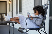 Kid toddler girl sitting in the park house porch playing with smartphone latin ethnicity