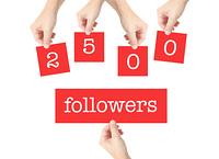 2500 followers written on cards held by hands