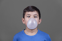 A young boy looks down, cross eyed like,  at the bubble he blew with gum