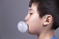 Close up of boy blowing bubble.. The close up side profile of a boy blowing a bubble from gum.