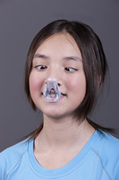 Girl looks at popped gum on her nose.. A girl has a cross eyed look as she looks at the popped gum mess on her nose.