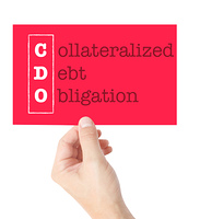 Collateralized Debt Obligation explained on a card held by a hand