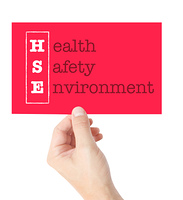 Health Safety Environment explained on a card held by a hand