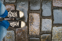 Teenage legs in sneakers and blue jeans standing on wet paving stones, top view, unusual perspective