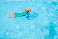 Young child swimming with arm bands