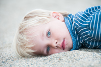 A portrait of a boy laying in the sand