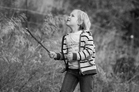Boy with a stick playing outdoors