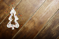 Christmas tree paper cutout background on wooden table