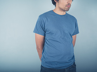 A young man wearing a t-shirt is standing by a blue wall