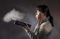 Asian woman blows dust off an old dictionary in this concept image.. Blowing dust off a book.