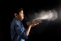 Boy blows dust off book.. A young boy blows dust off a book in this conceptual image.