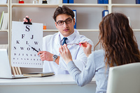 The doctor optician with letter chart conducting an eye test check. Doctor optician with letter chart conducting an eye test check