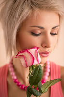 Young beautiful woman holding bouquet of pink roses. She is very satisfacted. Valentine's day or international women's day celebration.