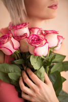 Unrecognizable woman holding bouquet of pink roses. She is very satisfacted. Valentine's day or international women's day celebration.