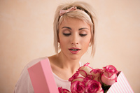 Young beautiful woman holding bow with bouquet of pink roses inside. She is very satisfacted. Valentine's day or international women's day celebration.