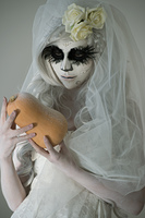 Halloween witch. Beautiful woman wearing santa muerte mask holding pumpkin