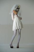 Halloween witch. Beautiful woman wearing santa muerte mask and wedding dress holding pumpkin posing full length