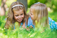 Two little sisters having fun in summer park while laying on lawn