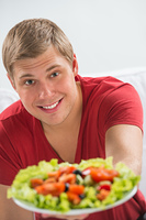Young man eating vegetarian salad with appetite