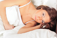 Beautiful serious woman lying on her bed
