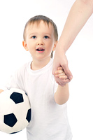 LIttle boy holding a soccer ball hand in hand with parent