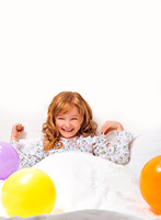 Smiley little girl in bed surrounded by coloured ballon