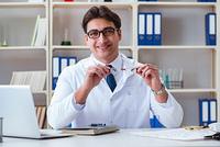 Doctor optician prescribing holding optical glasses