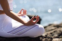 Young woman doing yoga in the beach. Female wearing sport clothes in lotus figure with defocused background.