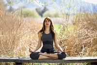 Young woman doing yoga in nature. Female wearing sport clothes in lotus figure.