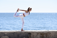 Young woman doing yoga in the beach. Female wearing sport clothes with defocused background.