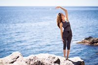 Young woman doing yoga in the beach. Female wearing sport clothes with defocused sea background.