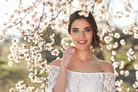 Portrait of young woman smiling in the flowered garden in the spring time. Almond flowers blossoms. Girl dressed in white like a bride.
