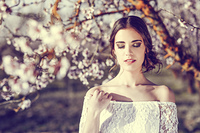 Portrait of young woman in the flowered garden in the spring time. Almond flowers blossoms. Girl dressed in white like a bride.