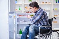 Young disabled injured man opening the fridge door . The young disabled injured man opening the fridge door