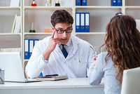 Doctor optician prescribing glasses to a patient