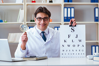 Doctor optician with letter chart conducting an eye test check
