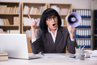 Angry businesswoman shouting with loudspeaker