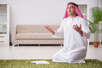 Arab man praying at home