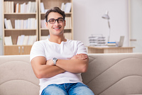 Young man relaxing sitting in couch sofa