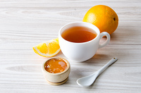 Cup of tea served with orange jam