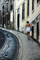 Young woman walks uphill in Lisbon, Portugal in a white dress
