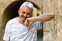 Mature man smiling at camera in urban background. Senior male with white hair and beard wearing casual clothes.