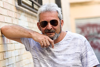 Mature man smiling at camera in urban background. Senior male with white hair and beard wearing casual clothes and aviator sunglasses.