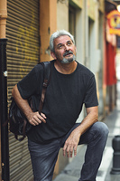 Mature tourist man in urban background. Mature male with white hair and beard wearing casual clothes and travel backpack